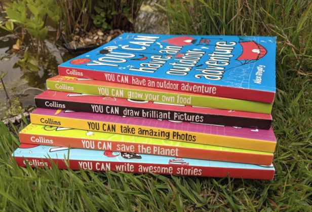 Six brightly coloured books all entitled 'You Can' piled in grass