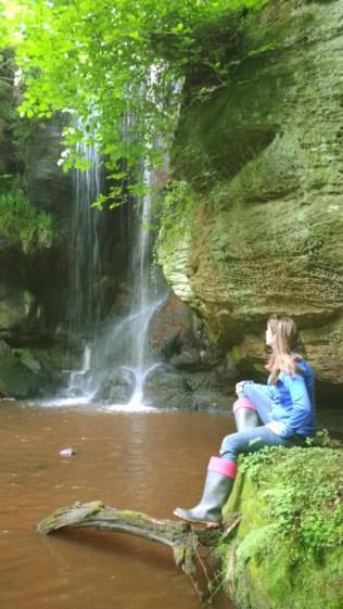 Woman sitting by waterfall