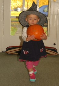 toddler-in-witches-hat-carrying-pumpkin
