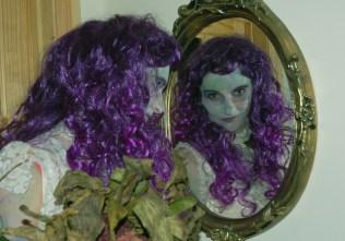 woman-looking-in-mirror-with-purple-wig-halloween-fancy-dress