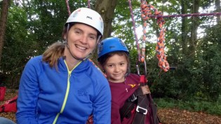 woman-and-girl-in-helmets-with-climbing-harness-near-tree