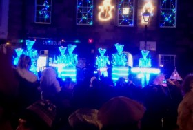 band-of-drummers-in-light-suits-and-white-makeup-on-platform-with-crowd-watching