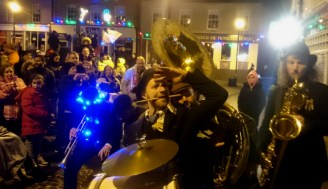 brass-quartet-playing-in-street-with-crowd-and-christmas-lights