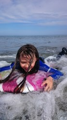 Girl on bodyboard with white water in sea close up