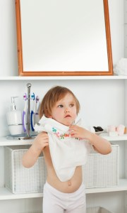 Small girl changing clothes in bathroom