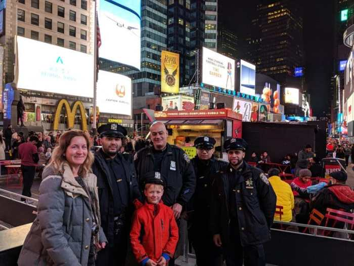 Vibrant Time Square in New York with kids having a photo with New York City cops