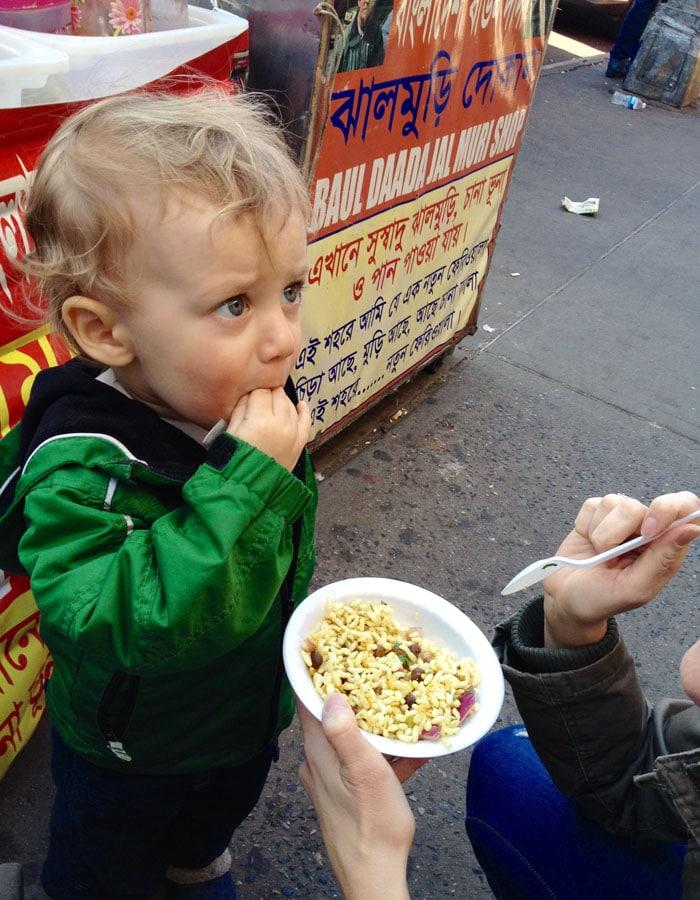 Toddler eating Bengali street food in Queens