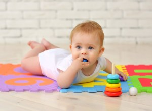 baby plays on the floor with toys and stuffs small parts into his mouth.