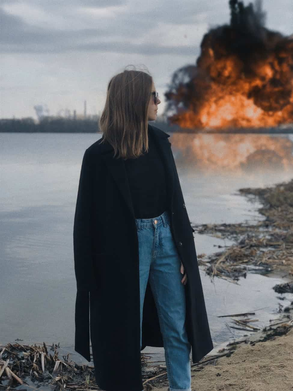 Boom woman in black coat standing near body of water