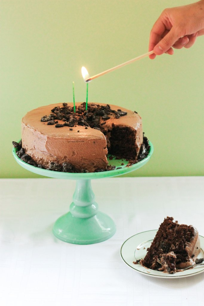 Devil's food cake with mocha frosting hand lighting a candle