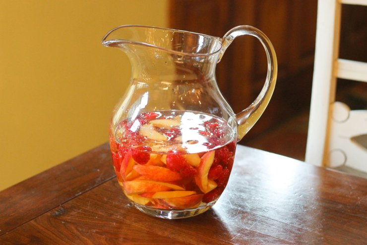 Peaches and raspberries in a pitcher to make sangria