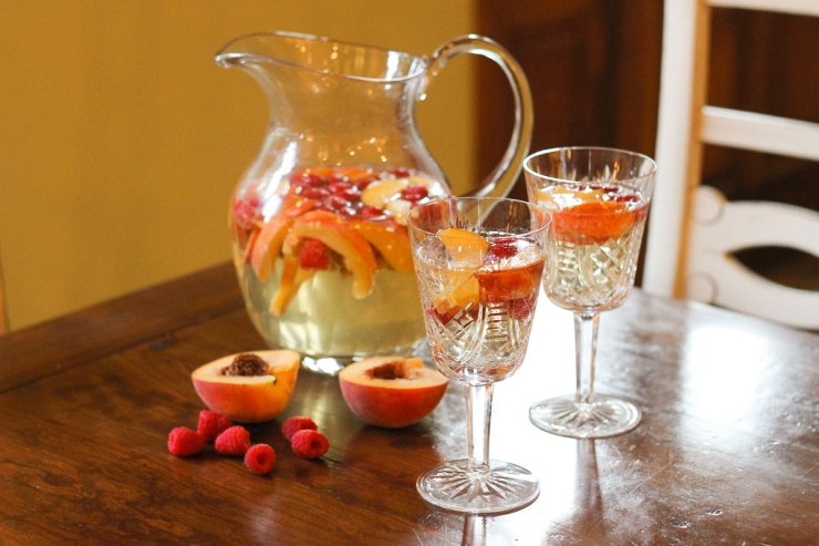 Sparkling peach sangria in a pitcher with glasses ready to serve.