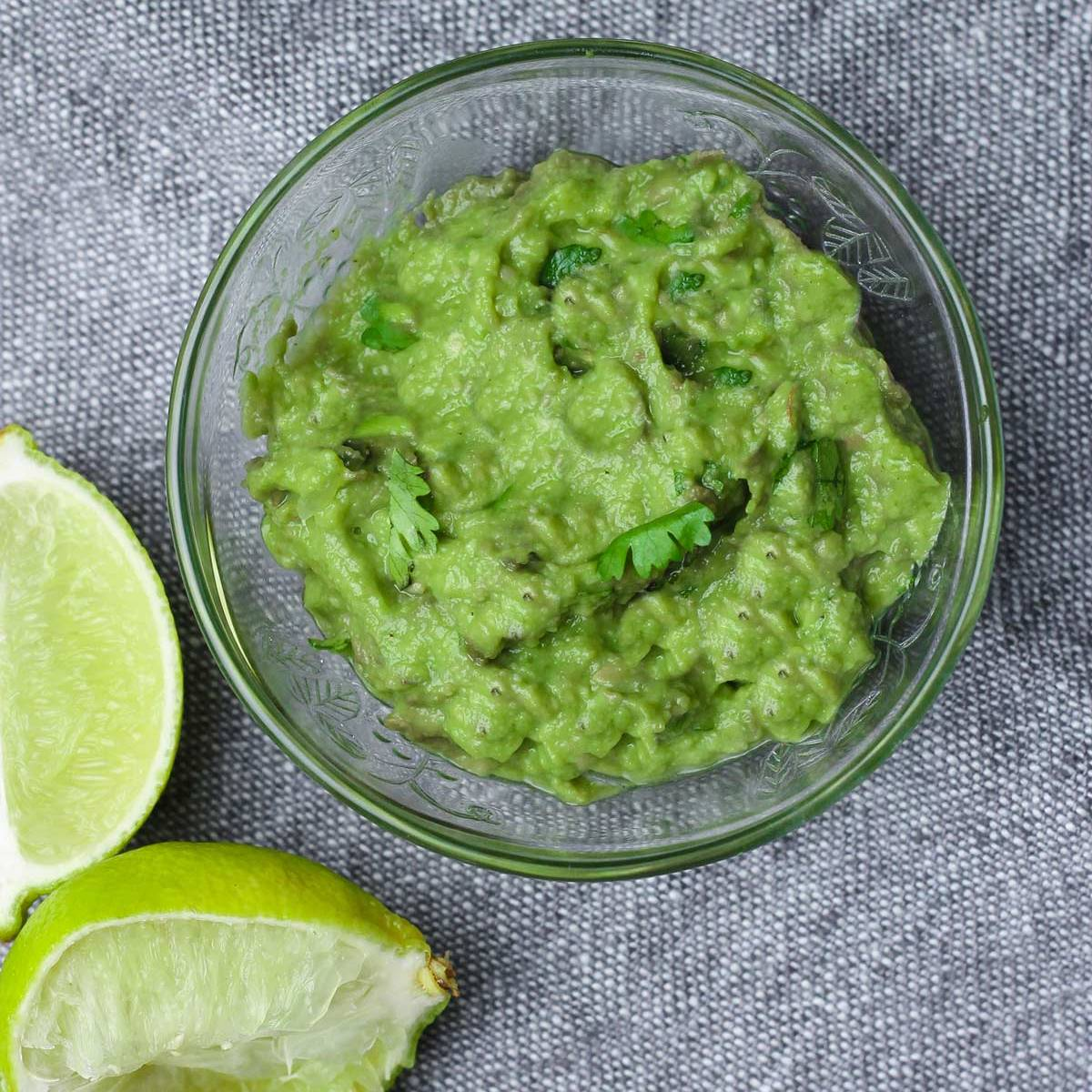 small bowl of guacamole with squeezed limes