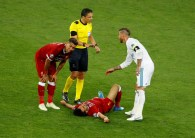 Soccer Football - Champions League Final - Real Madrid v Liverpool - NSC Olympic Stadium, Kiev, Ukraine - May 26, 2018 Liverpool's Mohamed Salah after sustaining an injury while Liverpool's Roberto Firmino looks on and Real Madrid's Sergio Ramos talks with referee Milorad Mazic REUTERS/Phil Noble