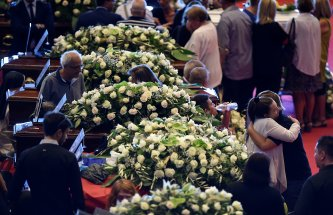 People mourn next to the coffins containing bodies of victims of the Genoa bridge collapse, at the Genoa Trade Fair and Exhibition Centre in Genoa, Italy August 18, 2018. REUTERS/Massimo Pinca