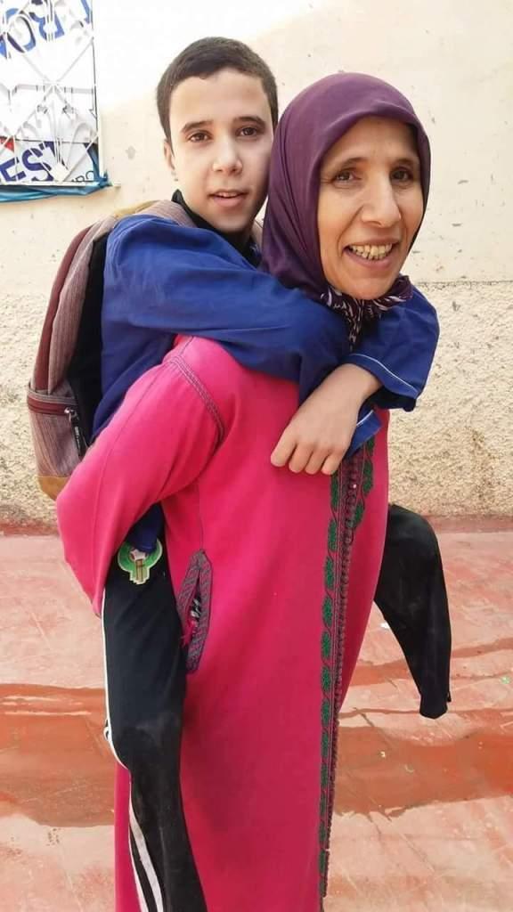 كتهزّ ولدها على ظهرها باش تدّيه يقرا.. قصة مؤلمة لأم تتألم كل يوم!! (فيديو)