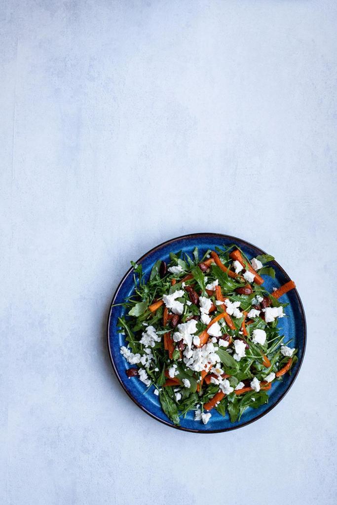 Lækker og farvefin salat af rucola, bagte gulerødder, mandler og feta