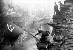 Orginal mit Armbanduhren2.5.1945May 2, 1945 Berlin. Chaldej took this photograph as the Russian troops celebrated below in the Reichstag, the seat of the German parliament. Because the dome on the top of the building was on fire, Chaldej and three Russian soldiers climbed out on one wing of the building in order to take photograph. It was important for Chaldej to photograph this victory with the background of the ruins and he took 36 shots in total. The three Soviet soldiers were from the Ukraine, Machatschkala in Dagestan and Russia. In the early hours of May 3, Chaldej was flown back to Moscow in order to present his material to Stalin. This image was processed and published immediately. It was later noticed that one of the flag bearers was wearing mulitple watches on his wrists which was evidence of his thievery. The photograph was then manipulated to create an official version.