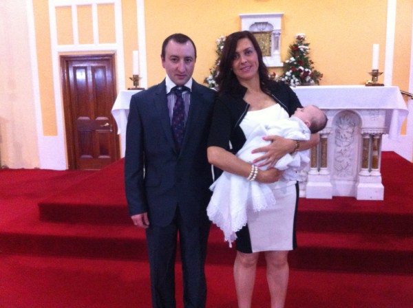 Alex James Michael with his parents Linda and Edward on his baptism day.
