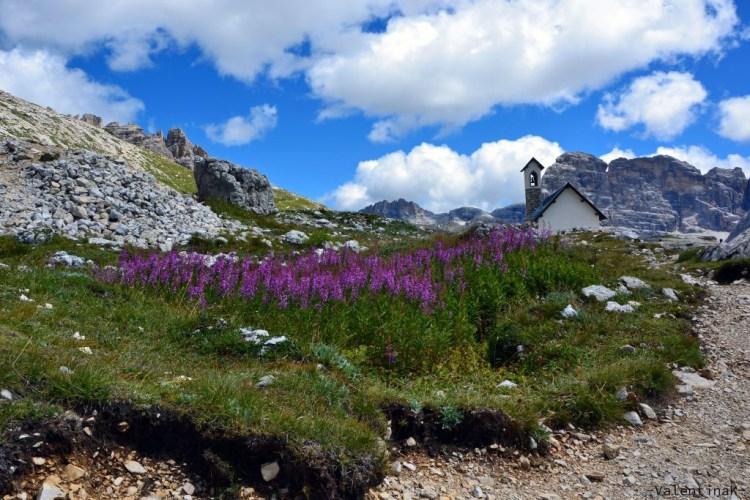 Fiori, chiesetta, montagne e nuvole intorno alle Tre Cime di Lavaredo