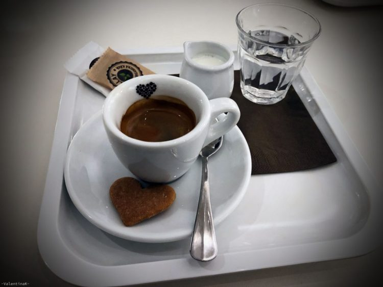 la pausa caffè perfetta, tazzina con espresso, brocca di latte, biscotto a forma di cuore