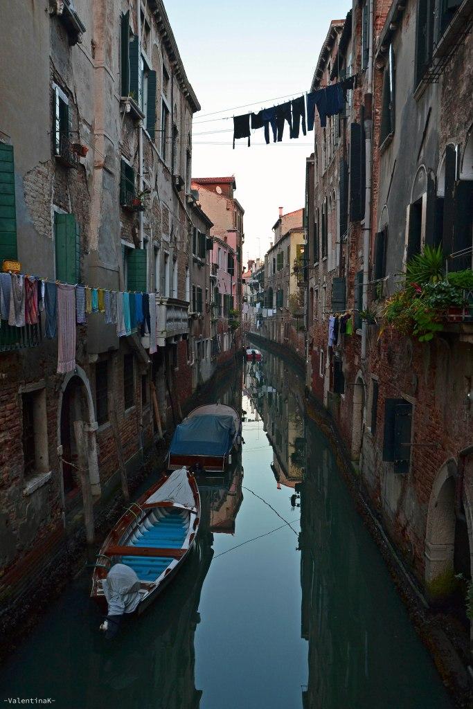 tipico angolo di venezia: un canale con barche e i panni stesi sopra