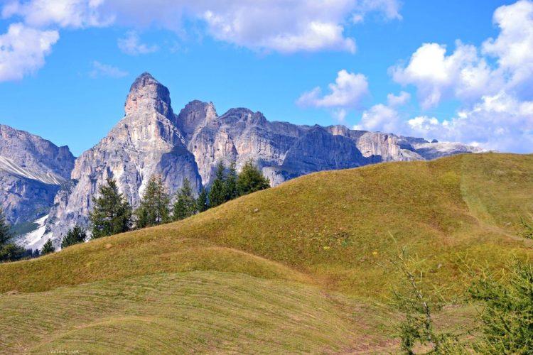 un mezzogiorno settembrino di montagna: la vetta del sassongher da dietro colline di prati