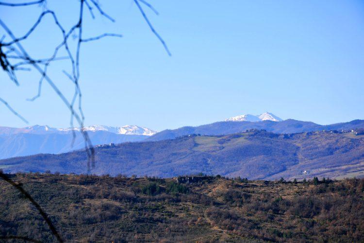 cimone semi-innevato e colline verdi