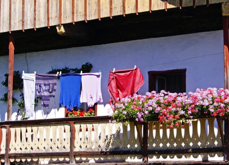 balcone di una casa a dobbiaco in val pusteria, con fiori e panni stesi