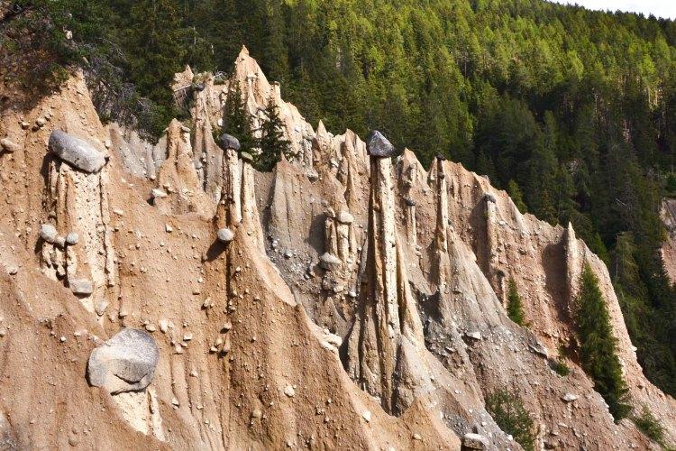 Piramidi di terra a Perca, pinnacoli d'argilla vertiginosi con rocce sulla sommità