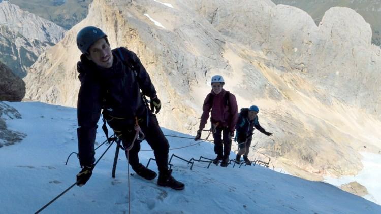 in cima alla marmolada: escursionisti sulla lunghissima scala metallica della via ferrata
