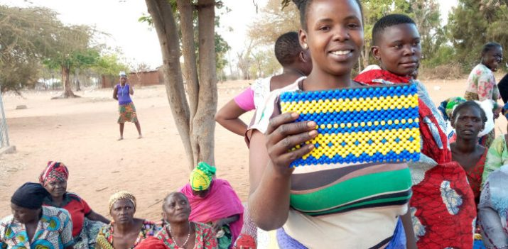 Young woman showing hand-made bag