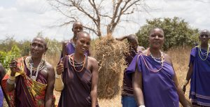 pastoralists proudly presenting hay bales
