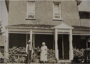 two unidentified people outside of a home
