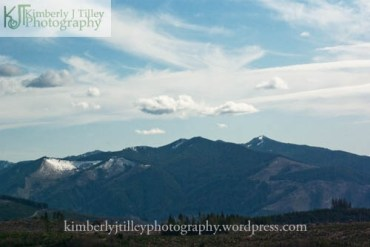assorted clouds hover over a mountain range