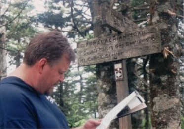 a man looks at a map in front of a trail sign
