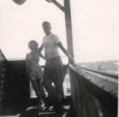a black and white photo of a young girl and her father on a platform above the town