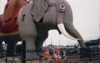 elephant-shaped building from the side with three children sitting on bleachers beside it