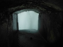 an arched tunnel of light with water dripping inside