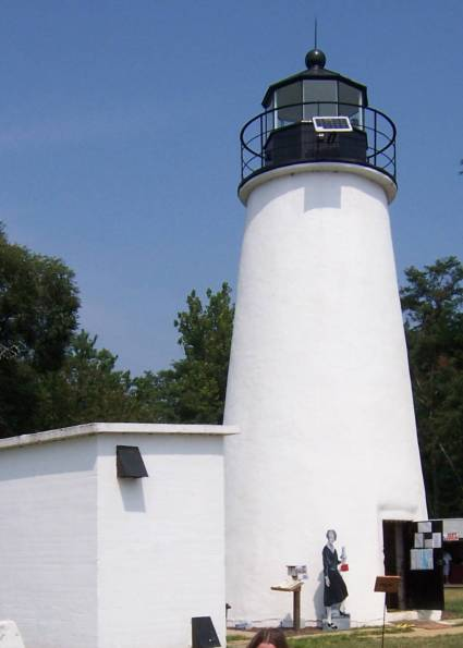 a white lighthouse and an adjacent white building