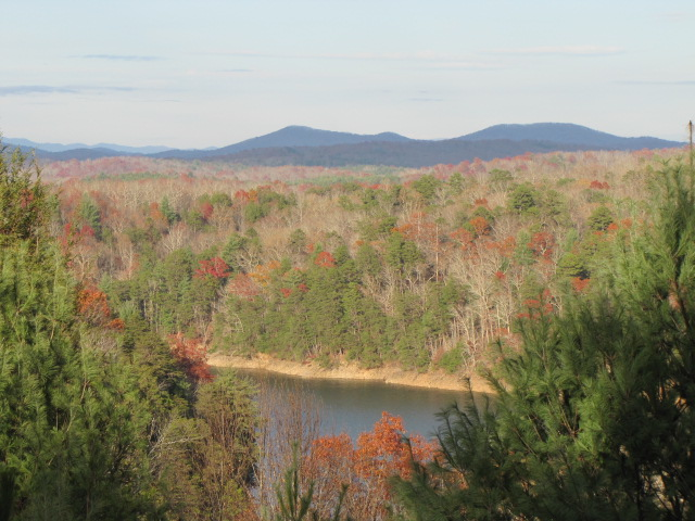 a lake surrounded by trees, some of which have started to turn red