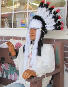 a Native American statue sitting on a bench
