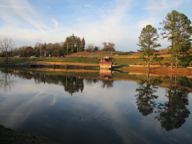 A large lake with a small building and tall trees on the far side. They are reflected in the water