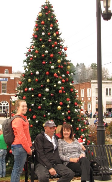 A bench in front of  a Christmas tree. A couple sits on the bench, a younger woman standa beside them