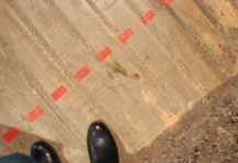 black boots between a red dotted line and a dirt wall