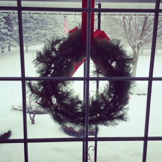View of a Christmas Eve snowstorm from indoors, with a wreath in the window. (2013)