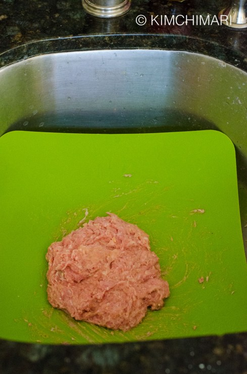 meatball mixture thrown on the plastic cutting board inside sink
