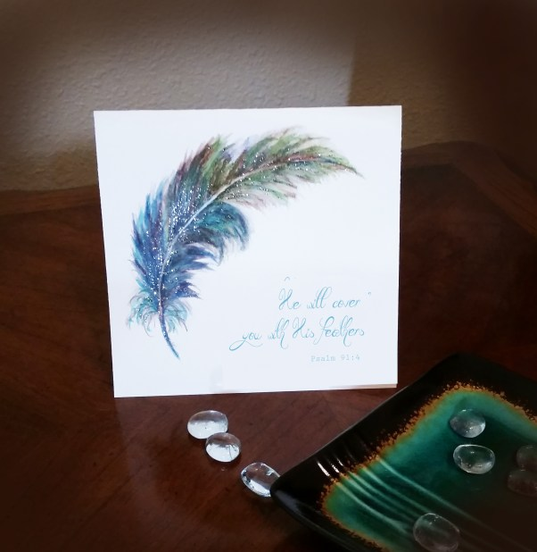 Watercolor Feather Card Image on brown table with turquoise plate