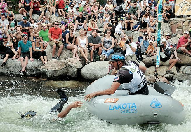 The crowd reacts as Masayuki Takahata, left, falls out of a raft and Todd Toledo reaches for him during a Teva Mountain Games Raft Cross event in Vail during the GoPro Games.
