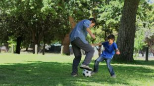 stock-footage-video-of-a-son-and-his-father-playing-football-in-a-park